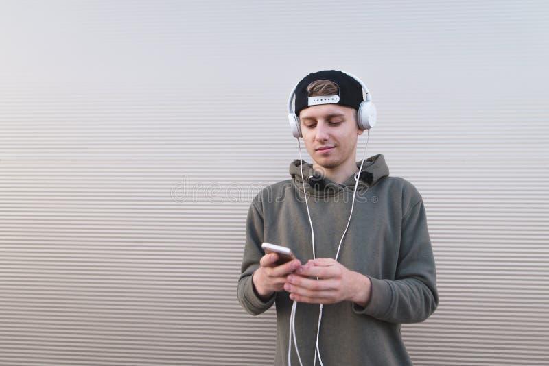 Ένας νεαρός άνδρας ακούει τη μουσική στα ακουστικά και εξετάζει το smartphone του στο υπόβαθρο ενός ελαφριού τοίχου στοκ φωτογραφίες