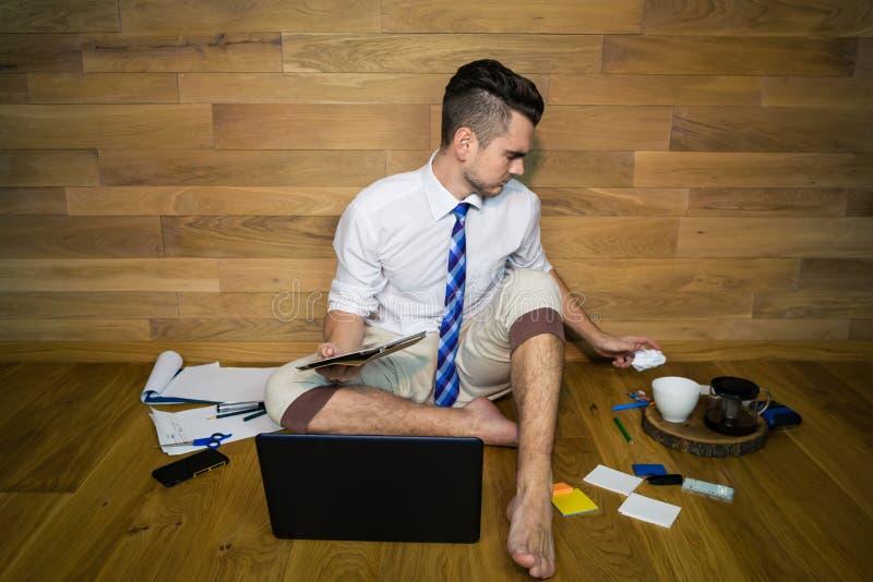 Ένας νεαρός άνδρας εργάζεται με το πρόγραμμα και ρίχνει έξω το φύλλο με τις κακές ιδέες στοκ εικόνα με δικαίωμα ελεύθερης χρήσης