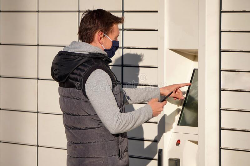 Ένας νεαρός άνδρας με μπλε μάσκα μαζεύει ένα πακέτο στο Box για δέματα Παράδοση αγαθών και προϊόντων χωρίς επαφή ή χωρίς επαφή στοκ φωτογραφία με δικαίωμα ελεύθερης χρήσης