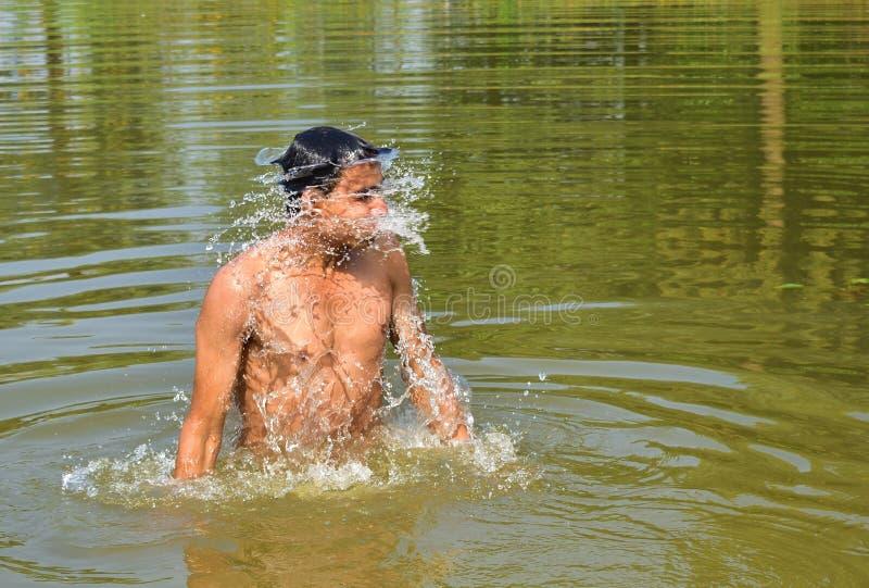 Ένας νεαρός άνδρας που κολυμπά στη λίμνη σε ένα θερινό μεσημέρι Θερινή κολύμβηση παιχνίδι με το νερό σε θερινή περίοδο στοκ εικόνες