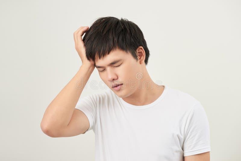 Ένας νεαρός άνδρας που κρατά το κεφάλι του με το χέρι του φαίνεται κουρασμένος με αυτός στοκ εικόνες με δικαίωμα ελεύθερης χρήσης