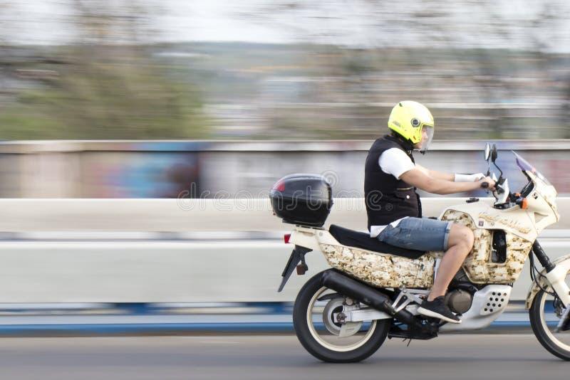 Ένας νεαρός άνδρας που οδηγά τη γρήγορη μοτοσικλέτα πέρα από τη γέφυρα οδών πόλεων στοκ φωτογραφία με δικαίωμα ελεύθερης χρήσης