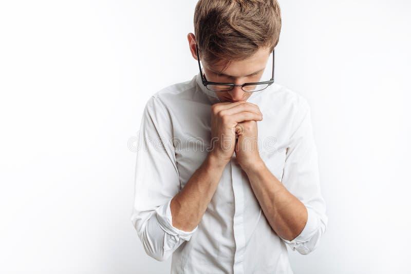 Ένας νεαρός άνδρας που προσεύχεται στο Θεό ή το Ιησούς Χριστό, που διπλώνεται, σε ένα άσπρο υπόβαθρο, που ζητά τη βοήθεια στοκ εικόνες