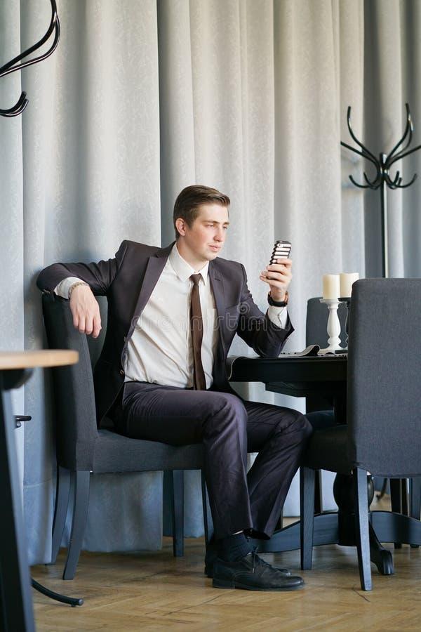 Ένας νεαρός άνδρας σε ένα μαύρο επιχειρησιακό κοστούμι, το λευκοί πουκάμισο και ο δεσμός που εξετάζουν τις ειδήσεις ταΐζουν με το στοκ φωτογραφίες