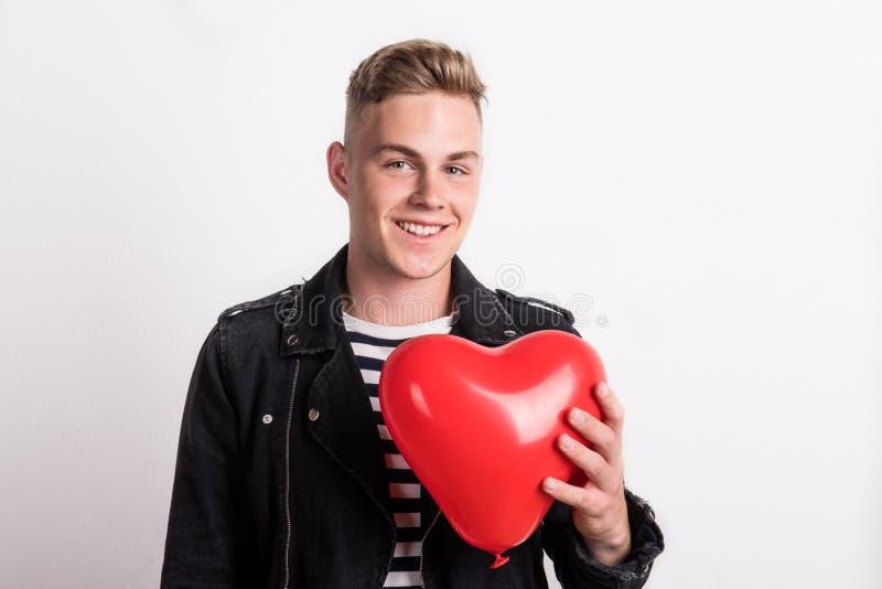 Ένας νεαρός άνδρας σε ένα στούντιο, που κρατά το κόκκινο μπαλόνι καρδιών μπροστά από τον στοκ φωτογραφίες
