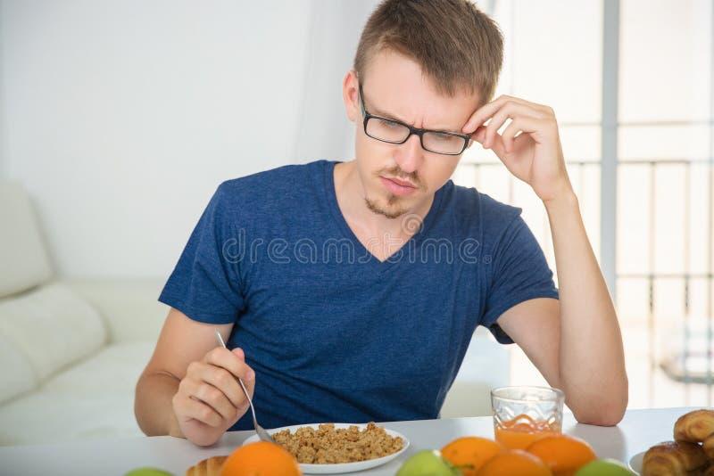 Ένας νεαρός άνδρας σκέφτηκε oatmeal κατά τη διάρκεια του προγεύματος στοκ φωτογραφία με δικαίωμα ελεύθερης χρήσης