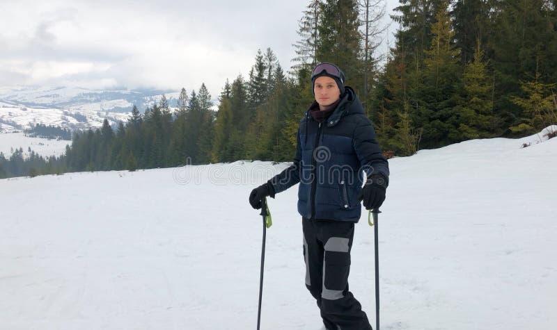 Ένας νεαρός άνδρας στα αθλητικά γυαλιά κάνει σκι στα βουνά στοκ φωτογραφίες