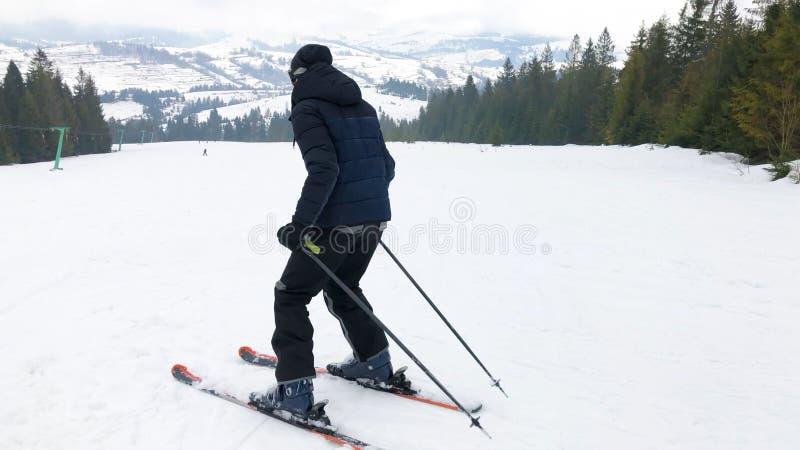 Ένας νεαρός άνδρας στα αθλητικά γυαλιά κάνει σκι στα βουνά στοκ φωτογραφίες με δικαίωμα ελεύθερης χρήσης
