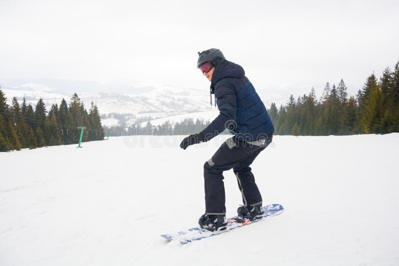 Ένας νεαρός άνδρας στα αθλητικά γυαλιά και στο κράνος οδηγά ένα χιόνι στοκ εικόνες