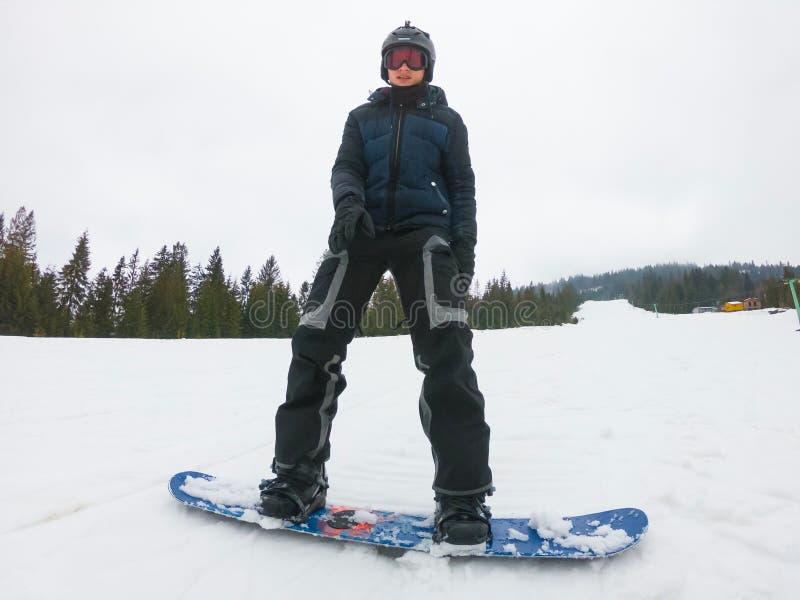 Ένας νεαρός άνδρας στα αθλητικά γυαλιά οδηγά ένα σνόουμπορντ στο υποστήριγμα στοκ φωτογραφία
