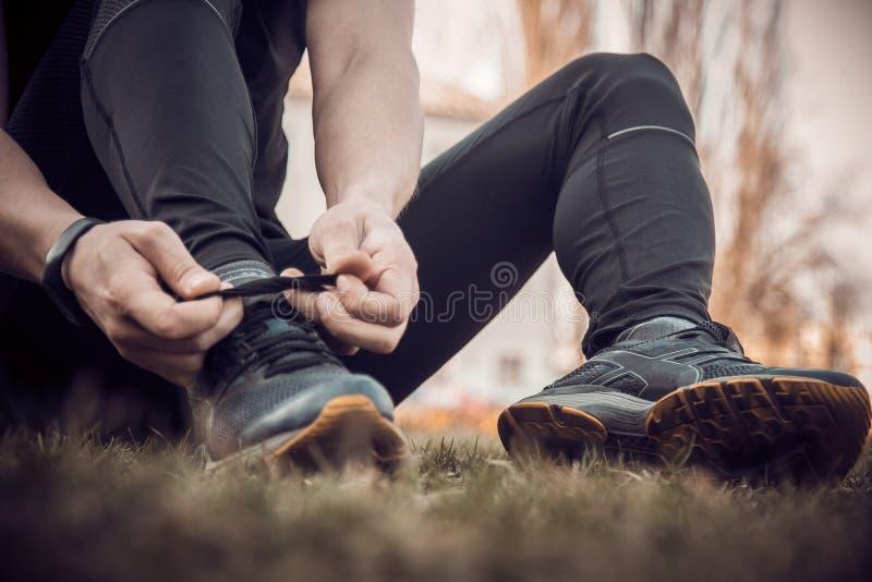 Ένας νεαρός άνδρας στα μαύρα ενδύματα εμπλέκει τις δαντέλλες στα πάνινα παπούτσια κοντά συνεδρίαση αθλητών ικανότητας στον αθλητι στοκ εικόνα με δικαίωμα ελεύθερης χρήσης