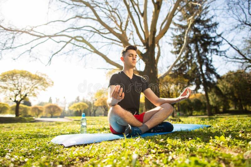 Ένας νεαρός άνδρας χαλαρώνει και κάνοντας τη γιόγκα στο πράσινο πάρκο Έννοια ενός υγιούς τρόπου ζωής στοκ εικόνα