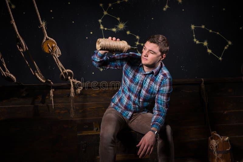 Ένας νεαρός άνδρας κάθεται σε ένα στήθος, εξετάζοντας το μπουκάλι γυαλιού και tryin στοκ εικόνες
