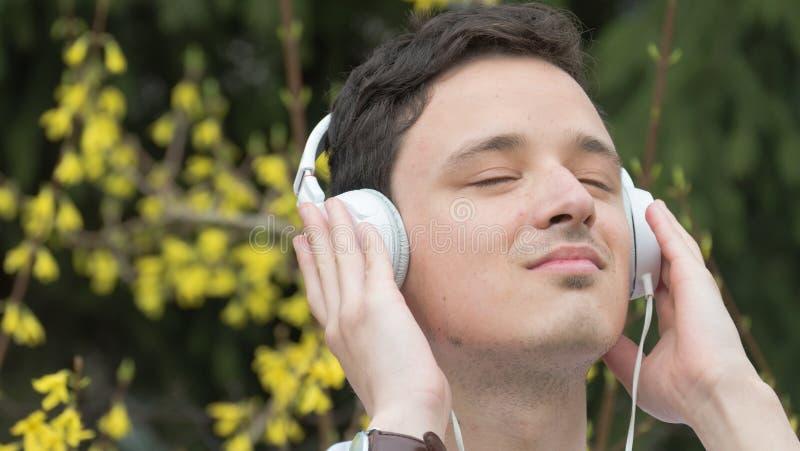 Ένας νεαρός άνδρας που ακούει τη μουσική από τα άσπρα ακουστικά στο πάρκο/το βοτανικό κήπο κατά τη διάρκεια του καλού χρόνου άνοι στοκ εικόνες