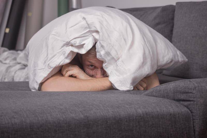Ένας νεαρός άνδρας που κρυφοκοιτάζει κάτω από το μαξιλάρι στοκ εικόνες με δικαίωμα ελεύθερης χρήσης
