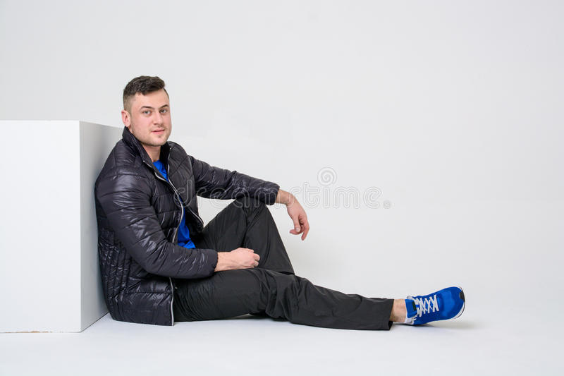 Ένας νεαρός άνδρας στα εσώρουχα, ένα σακάκι και τα πάνινα παπούτσια κάθεται την κλίση σε έναν άσπρο κύβο στοκ εικόνες με δικαίωμα ελεύθερης χρήσης