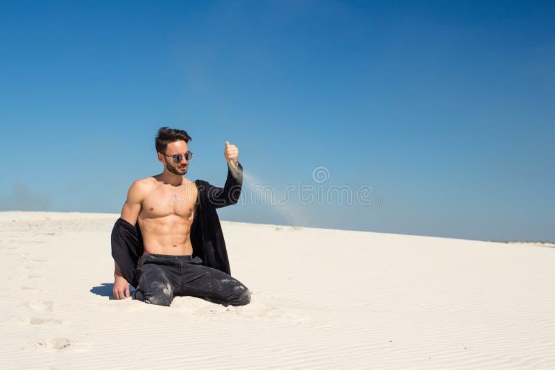 Ένας νεαρός άνδρας χύνει υπέροχα την άμμο με ένα χέρι στοκ φωτογραφία