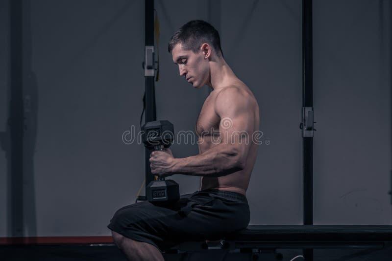 Ένας νεαρός άνδρας, bodybuilder συνεδρίαση, επίπεδος πάγκος, αλτήρας στοκ φωτογραφία