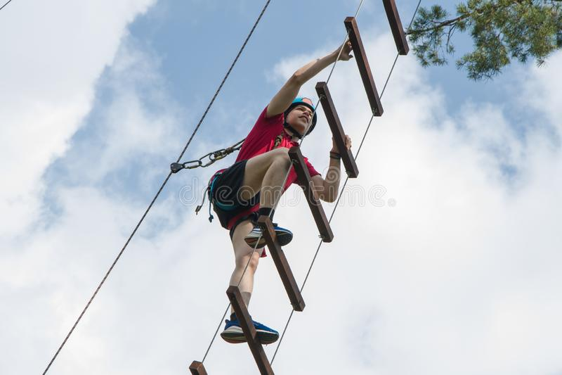 Ένας νεαρός με κράνος σκαρφαλώνει σε μια σκάλα με σχοινί στον γαλάζιο ουρανό Ορειβασία και αναρρίχηση για τουρίστες και παραθερισ στοκ εικόνες
