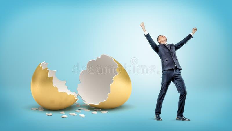 Ένας νικηφορόρος επιχειρηματίας στέκεται κοντά μεγάλο σπασμένο χρυσό eggshell στο μπλε υπόβαθρο στοκ εικόνες