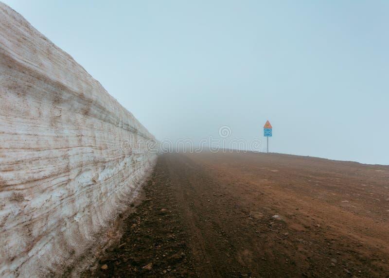 Ένας ομιχλώδης λασπώδης δρόμος δίπλα σε έναν τοίχο και τα οδικά σημάδια στοκ εικόνες με δικαίωμα ελεύθερης χρήσης