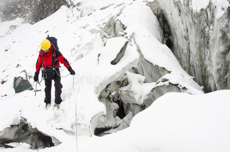 Ένας ορειβάτης νεαρών άνδρων διαβαίνει ένα crevasse στοκ εικόνες
