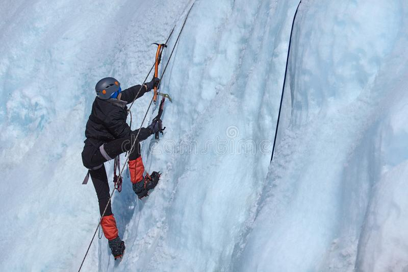 Ένας ορειβάτης πάγου κάνει τον τρόπο του σε έναν παγωμένο καταρράκτη στοκ φωτογραφίες με δικαίωμα ελεύθερης χρήσης