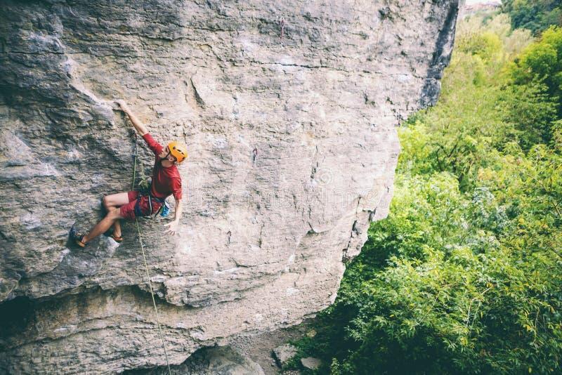Ένας ορειβάτης στο κράνος αναρριχείται στο βράχο στοκ φωτογραφίες