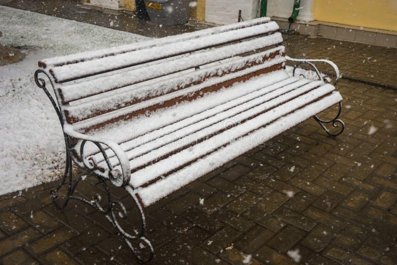 Ένας πάγκος που καλύπτεται ομαλά με το φρέσκο χιόνι μετά από τα καιρικά φαινόμενα στοκ εικόνες