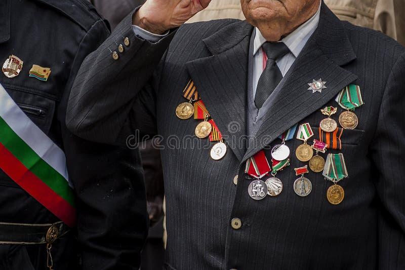 Ένας παλαίμαχος που διακοσμείται με τα μετάλλια και τις διαταγές σχετικά με το κοστούμι δίνει την τιμή κατά τη διάρκεια μιας παρέ στοκ φωτογραφίες με δικαίωμα ελεύθερης χρήσης