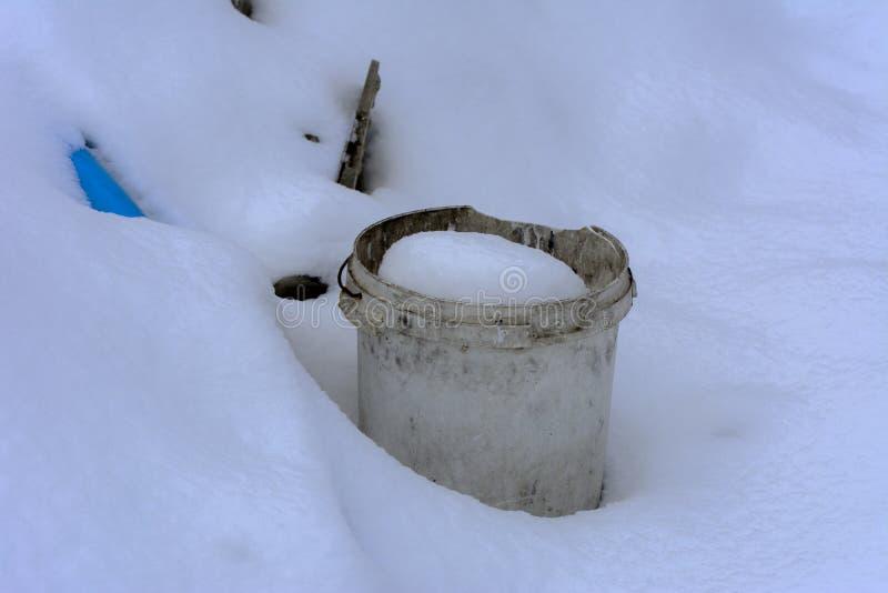 Ένας παλαιός άσπρος πλαστικός κάδος ρίχνεται το χειμώνα στοκ εικόνες