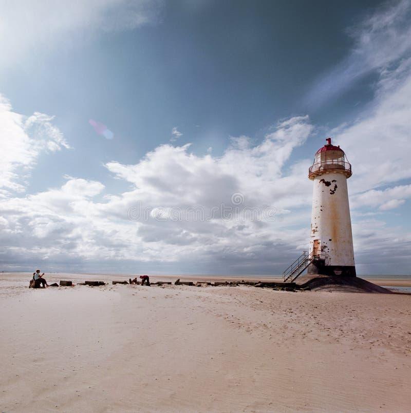 Ένας παλαιός άσπρος φάρος με μια κόκκινη στέγη σε μια αμμώδη παραλία και μια διάβαση στο μέτωπο με τη θάλασσα και ουρανός στο υπό στοκ φωτογραφίες