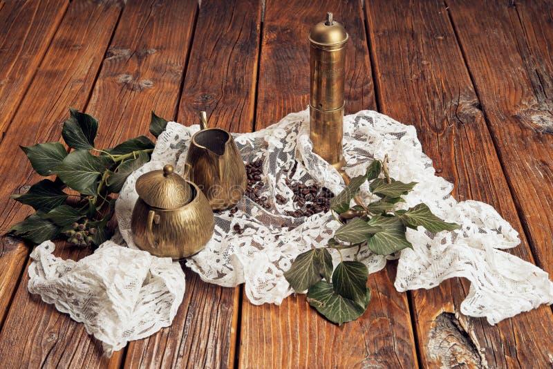 Ένας παλαιός μύλος καφέ φιαγμένος από ορείχαλκο, μια κανάτα γάλακτος ορείχαλκου και μια ζάχαρη ορείχαλκου κυλούν, παρουσιασμένος  στοκ φωτογραφίες με δικαίωμα ελεύθερης χρήσης
