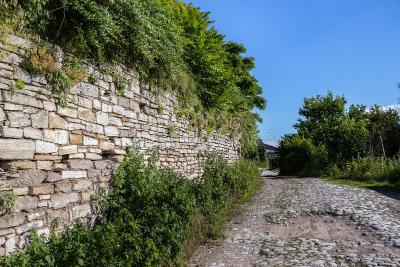 Ένας παλαιός πέτρινος-στρωμένος δρόμος που περνά έναν αρχαίο τοίχο πετρών που καλύπτεται μετά από με την πρασινάδα στοκ εικόνες