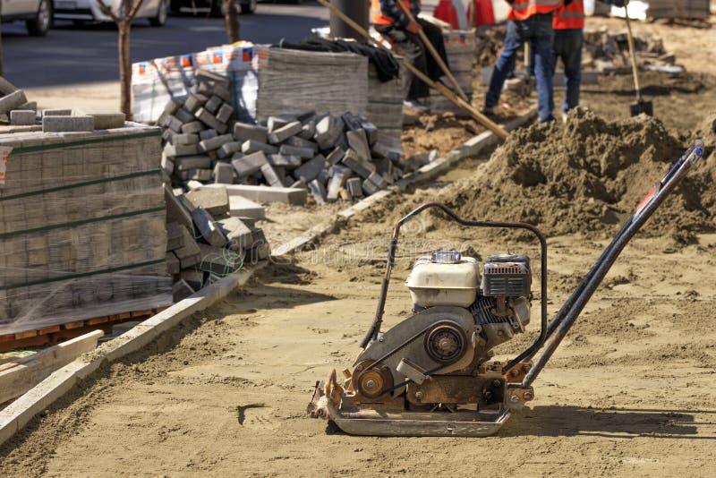 Ένας παλαιός συμπιεστής βενζίνης για τη συμπίεση του αμμώδους χώματος στέκεται απέναντι από έναν σωρό των πλακών επίστρωσης και μ στοκ φωτογραφία με δικαίωμα ελεύθερης χρήσης
