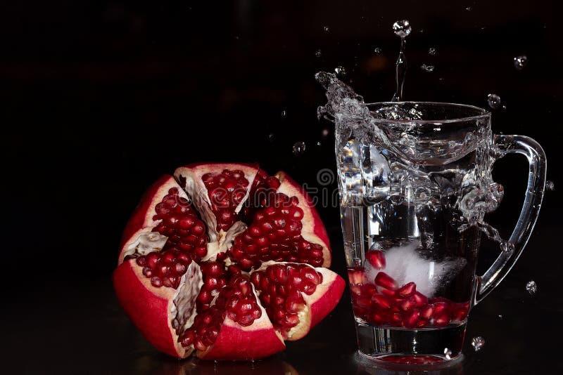 Ένας παφλασμός του ροδιού που στηρίζεται σε ένα γυαλί με τον πάγο και τα ακατέργαστα ανοιγμένα φρούτα που επιδεικνύονται στο αρισ στοκ φωτογραφία με δικαίωμα ελεύθερης χρήσης