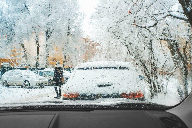 Ένας πεζός διασχίζει το δρόμο με χιονοθύελλα μπροστά από το αυτοκίνητο Οδός της πόλης το χειμώνα με χιονοθύελλα Σταγόνες παγωμένη στοκ φωτογραφία