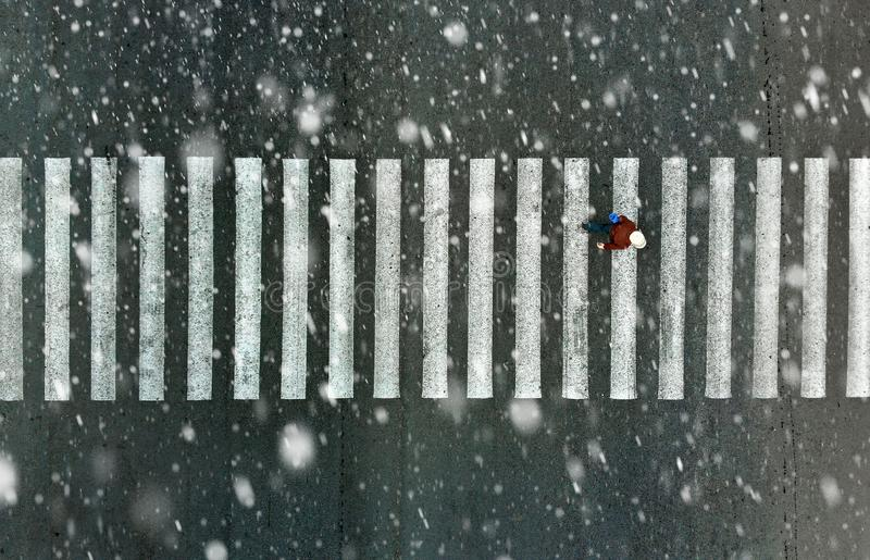 Ένας πεζός σε μια διάβαση πεζών όταν είναι χιονοπτώσεις στοκ φωτογραφία με δικαίωμα ελεύθερης χρήσης