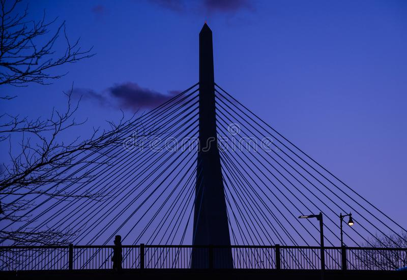 Ένας πεζός της Βοστώνης στο σούρουπο με τη γέφυρα Zakim που εμφανίζεται στο υπόβαθρο στοκ φωτογραφία με δικαίωμα ελεύθερης χρήσης