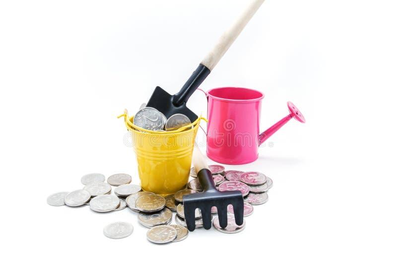Ένας πλήρης κάδος των χρημάτων και ενός φτυαριού στοκ εικόνα