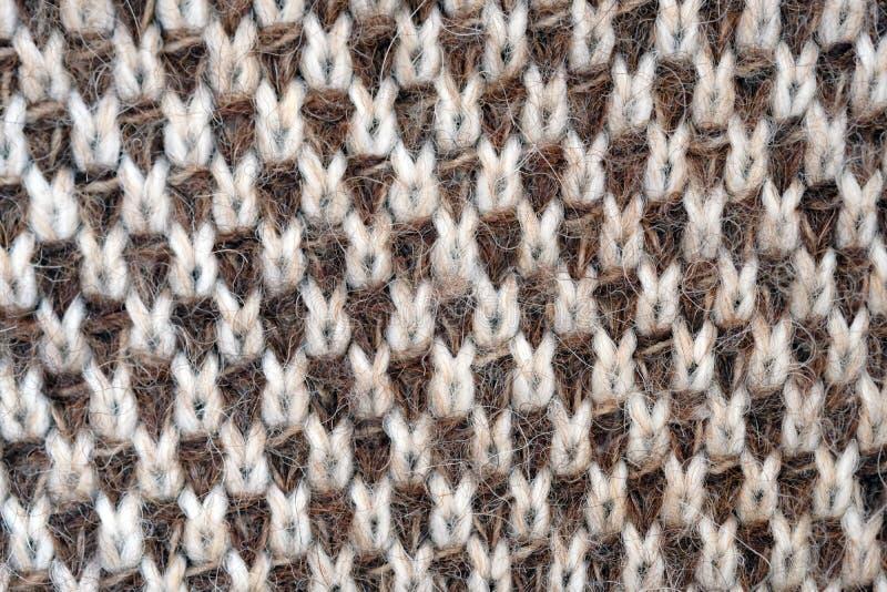 Ένας πλεκτός καμβάς με νήματα από ύφασμα Πουλόβερ πλεκτά από καφέ και λευκά νήματα στοκ εικόνες