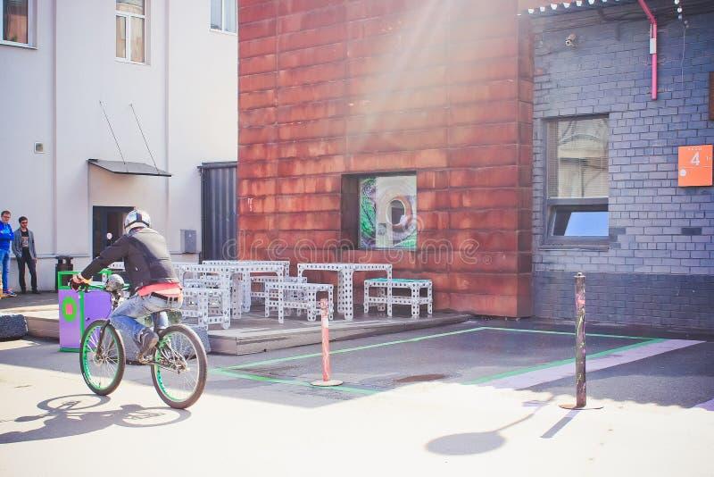 Ένας ποδηλάτης οδηγά τους προηγούμενους πίνακες και τις καρέκλες από ένα μεγάλο κτήριο που τίθεται στο εργοστάσιο σχεδίου Flacon στοκ εικόνες