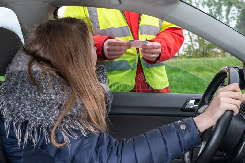 Ένας πολιτικός αστυνομικός ελέγχει την άδεια μιας νέας γυναίκας στο αυτοκίνητο στοκ φωτογραφία με δικαίωμα ελεύθερης χρήσης