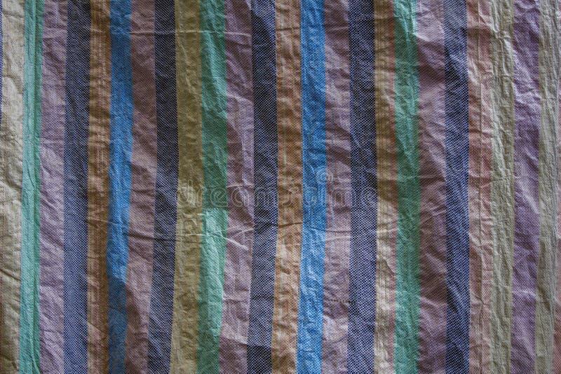 Ένας πολύχρωμος πυκνός καμβάς ζάρωσε το ύφασμα με τις κάθετες γραμμές Σύσταση τραχιάς επιφάνειας στοκ φωτογραφία