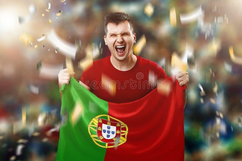 Ένας πορτογαλικός ανεμιστήρας, ένας ανεμιστήρας ενός ατόμου που κρατά τη εθνική σημαία της Πορτογαλίας στα χέρια του Ανεμιστήρας  στοκ φωτογραφία