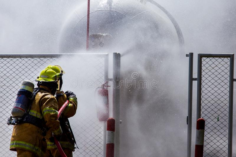 Ένας πυροσβέστης ελέγχει μια φωτιά στοκ εικόνα