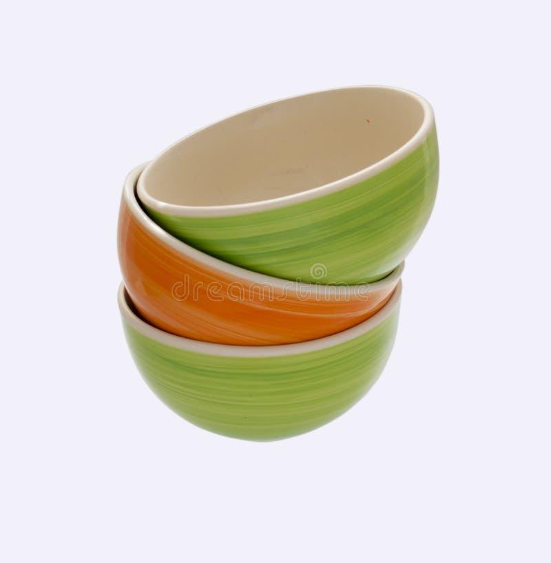 Ένας πύργος των πράσινων και πορτοκαλιών κεραμικών πιάτων, φυσικό φωτεινό χρώμα στοκ εικόνα