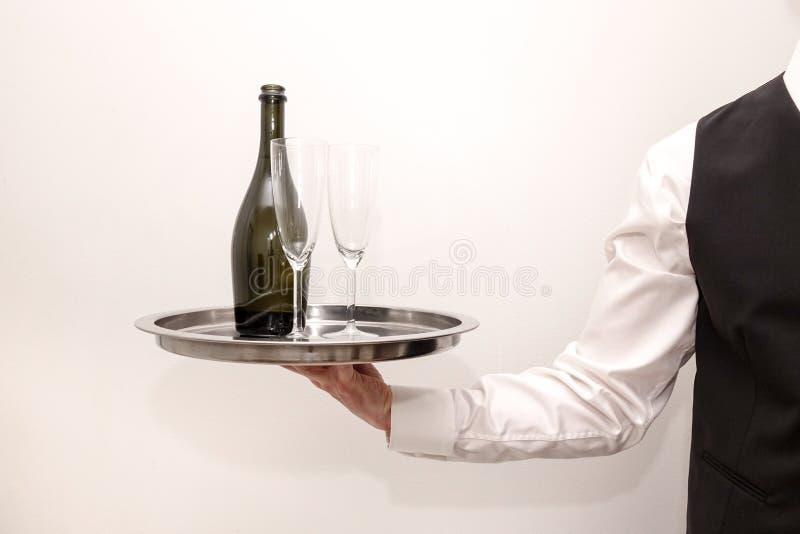 Ένας σερβιτόρος/ένας οικονόμος που φέρνει έναν ασημένιο δίσκο με ένα μπουκάλι της σαμπάνιας στοκ φωτογραφίες