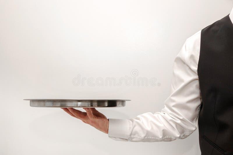 Ένας σερβιτόρος/ένας οικονόμος που φέρνει έναν κενό ασημένιο δίσκο στοκ εικόνες