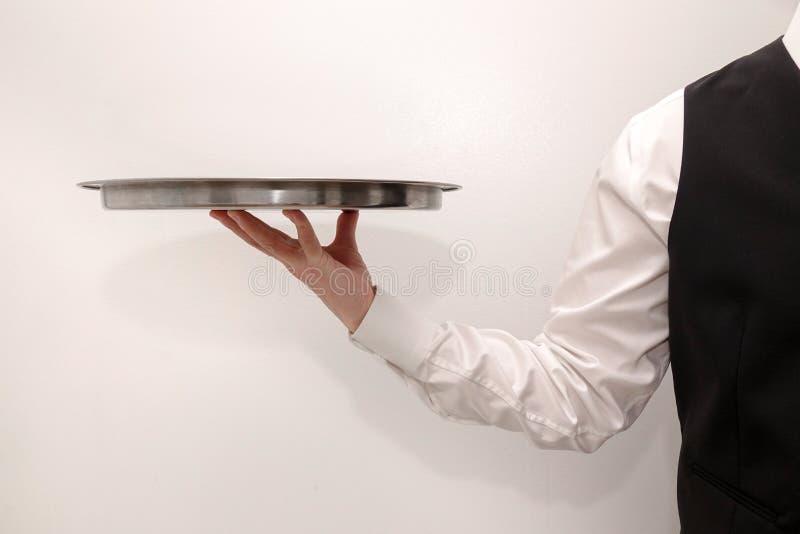 Ένας σερβιτόρος/ένας οικονόμος που φέρνει έναν κενό ασημένιο δίσκο στοκ φωτογραφίες